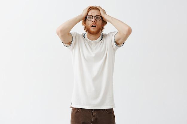 Смущенный бородатый рыжий парень позирует у белой стены в очках