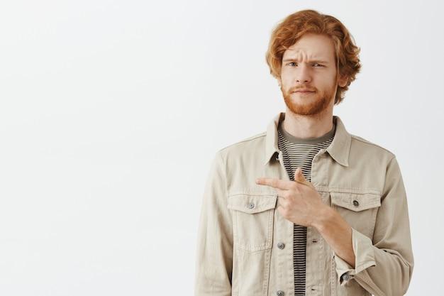 白い壁に向かってポーズをとっている混乱したひげを生やした赤毛の男