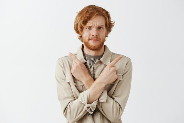 Смущенный бородатый рыжий парень позирует у белой стены