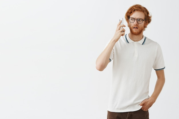 Confused bearded redhead guy posing against the white wall with glasses