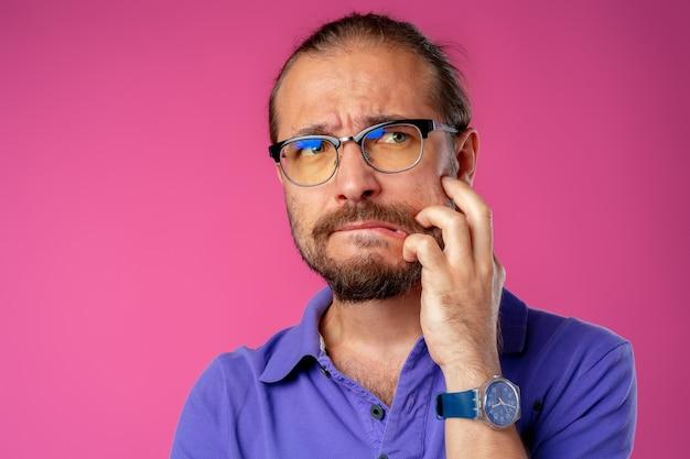 Смущенный бородатый молодой человек думает о чем-то крупным планом