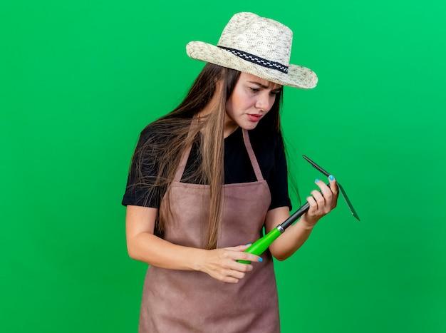 Смущенная красивая девушка-садовник в униформе в садовой шляпе держит и смотрит на грабли мотыги, изолированные на зеленом фоне