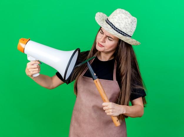 Смущенная красивая девушка-садовник в униформе в садовой шляпе, держащая и смотрящая на громкоговоритель с граблями, изолированными на зеленом