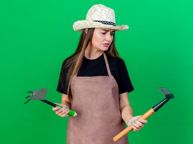 Смущенная красивая девушка-садовник в униформе в садовой шляпе держит грабли для мотыги и смотрит на грабли в руке, изолированной на зеленом фоне