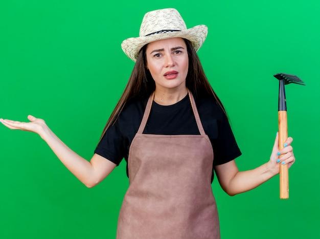 Смущенная красивая девушка-садовник в униформе в садовой шляпе, держащая грабли, раздвинула руку, изолированную на зеленом