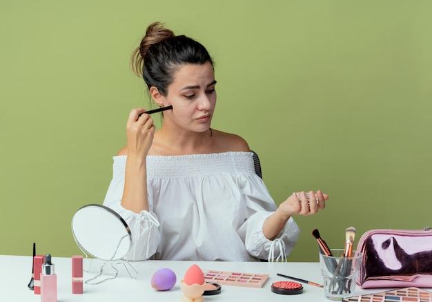 La bella ragazza confusa si siede al tavolo con gli strumenti di trucco tiene l'eyeliner e guarda l'ombretto isolato sulla parete verde