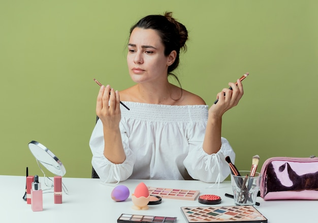 Confused beautiful girl sits at table with makeup tools holds makeup brushes isolated on green wall