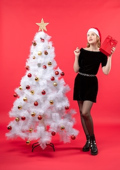 Confused beautiful woman in black dress and santa claus hat standing near white christmas tree