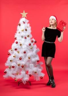 白いクリスマスツリーの近くに立っている黒いドレスとサンタクロースの帽子の混乱した美しい女性