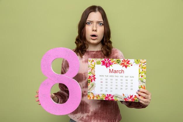 Bella ragazza confusa sulla festa della donna felice che tiene il numero otto con il calendario