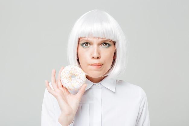 甘いドーナツを保持している混乱した美しい若い女性