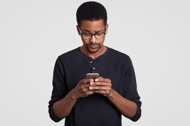 混乱している黒人アフロアフリカ人男性が携帯電話でファイルをダウンロード