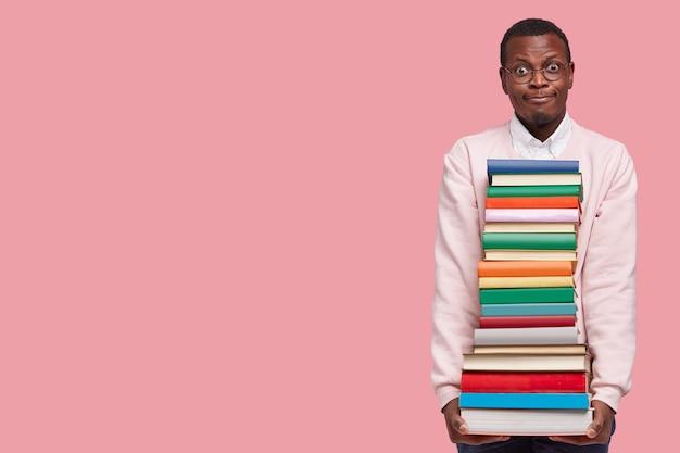 Uomo nero confuso trasporta una pila di libri, vestito con un maglione casual, indossa occhiali da vista