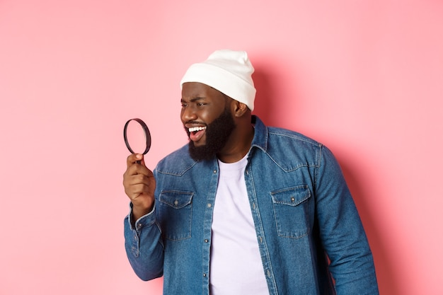 Confused black man looking through magnifying glass at something strange, standing over pink background