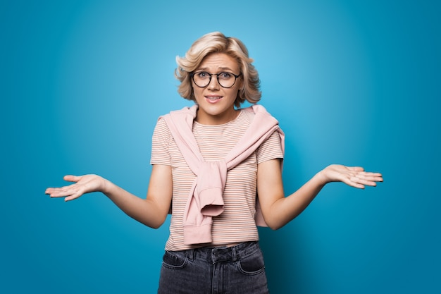 Confused blonde woman gesturing with palms at looking at camera through glasses on a blue studio wall