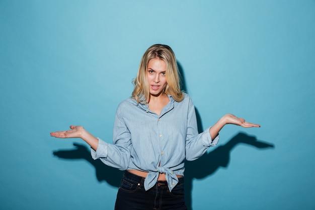Смущенная белокурая женщина в рубашке пожимает плечами