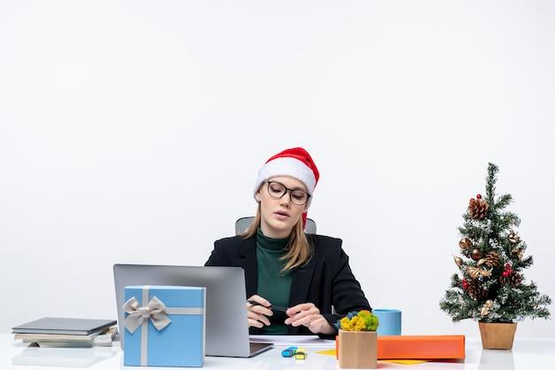 クリスマスツリーとその上に贈り物とテーブルに座って、白い背景の上のオフィスで何かを注意深く見ているサンタクロースの帽子と混乱した金髪の女性
