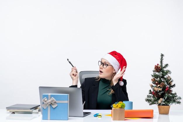 Смущенная блондинка в шляпе санта-клауса сидит за столом с елкой и подарком на ней на белом фоне