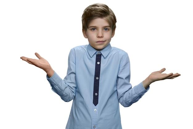 Смущенный мальчик делает жест на белой стене