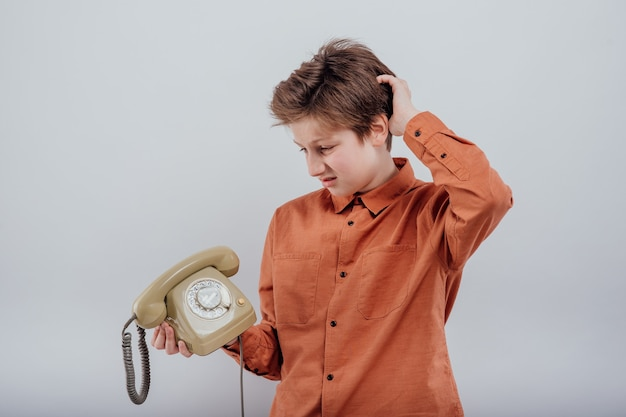 흰색 배경에 고립 된 오래 된 전화와 혼란된 소년