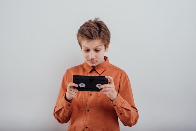 흰색 배경에 고립 된 비디오 카세트와 혼란된 소년