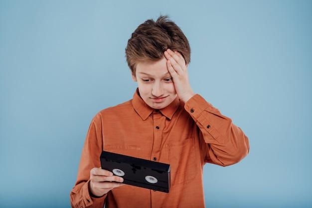 파란색 배경 오래된 가제트에 격리된 비디오 테이프로 혼란스러운 소년