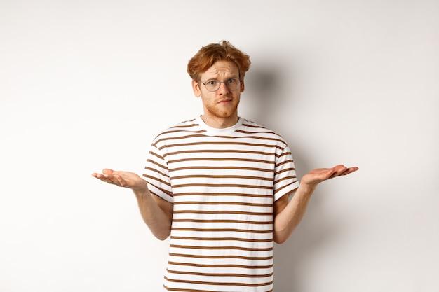 赤い髪の肩をすくめると混乱した彼氏は、手を横に広げ、カメラを見つめ、困惑し、何を尋ね、白い背景の上に足を踏み入れた。