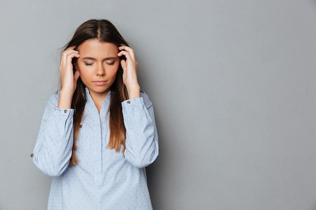 Confused brunette woman in shirt with closed eyes having headache