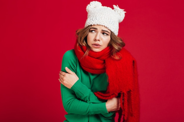 Confused brunette woman in sweater, funny hat and scarf
