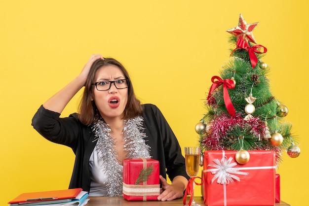 Signora di affari confusa in vestito con gli occhiali che tiene il suo regalo e che si siede a un tavolo con un albero di natale su di esso in ufficio