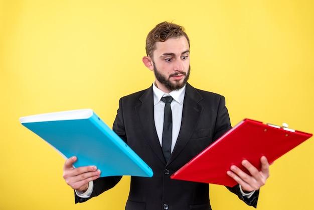 Persona di affari confusa che tiene due documenti con giacca e cravatta