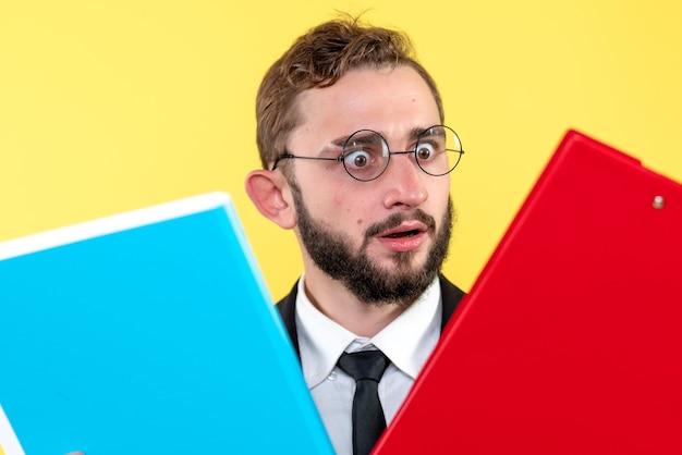 Uomo d'affari confuso con gli occhiali alla ricerca delle informazioni in due documenti