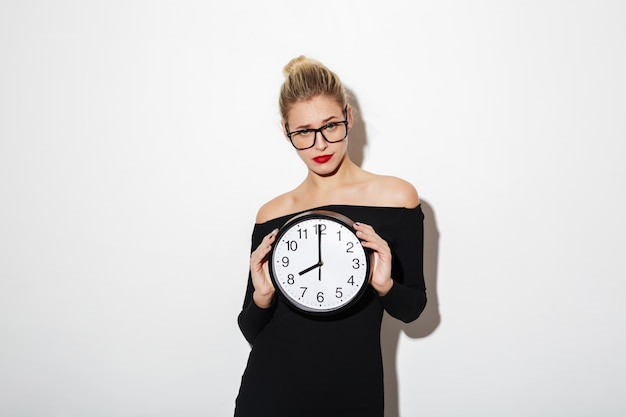 Confused business woman in dress and eyeglasses holding clock