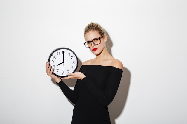 Confused business woman holding clock.