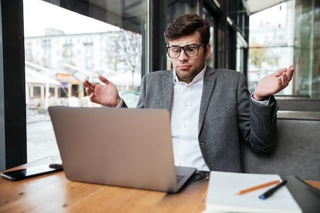 Смущенный бизнесмен в очках сидит за столом в кафе, пожимает плечами и смотрит на ноутбук