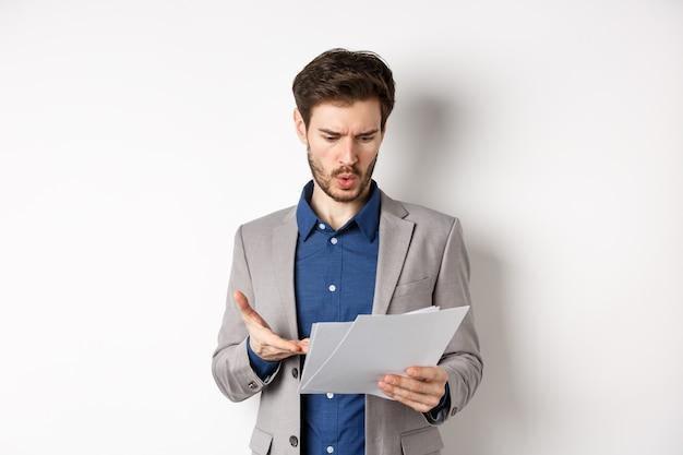 Путать бизнесмен, глядя на плохой документ, жалуясь на сделку, указывая на разочарованную бумагу, стоя в костюме на белом фоне.
