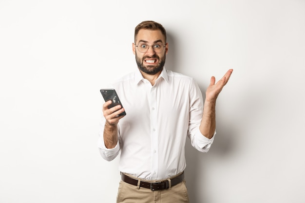 Путать бизнесмен, читая странное сообщение на мобильном телефоне, глядя раздраженным, стоя.