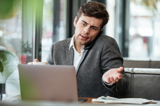 Confused businessman sitting by the table in cafe with laptop computer while talking by smartphone