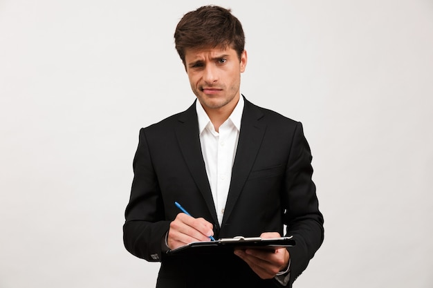 Confused businessman standing isolated holding clipboard.