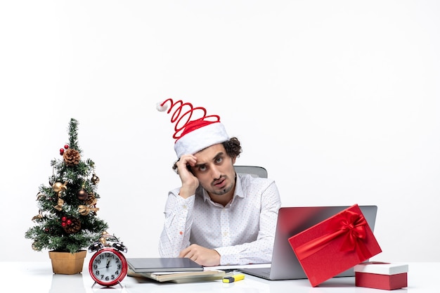 Смущенный занятый молодой бизнесмен с забавной шляпой санта-клауса, думающий о чем-то в офисе на белом фоне