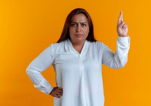 混乱したカジュアルな白人の中年女性が指を交差させ、腰に手を置く