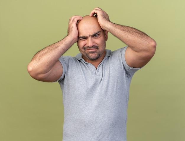 Uomo di mezza età casuale confuso che tiene le mani sulla testa isolata sulla parete verde oliva