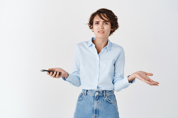 Confused caucasian woman shrugging with spread hands, holding mobile phone and looking puzzled, cant understand something strange, white wall
