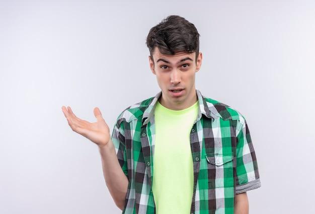 Giovane caucasico confuso che indossa la camicia verde tenuta a lato sul muro bianco isolato