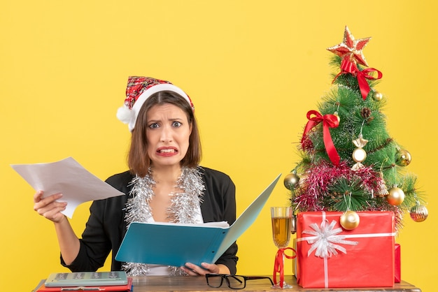 Confused charming lady in suit with santa claus hat and new year decorations holding document in the office on yellow isolated