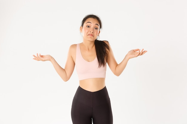 Confused and clueless asian fitness girl, female athlete in sportswear dont know, shrugging and grimacing puzzled, standing unaware white background.