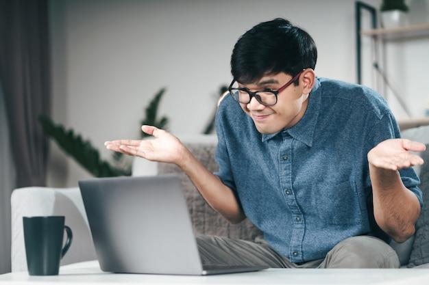ビデオ会議にラップトップコンピューターを使用している混乱した無知な男は、肩をすくめる肩をすくめて、私が知らないジェスチャーが何であれ、コンセプトを気にします