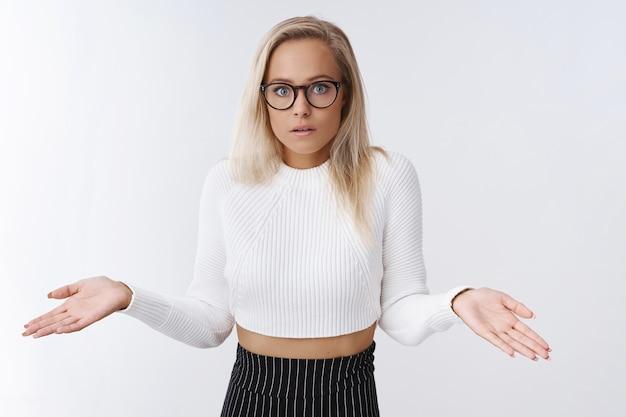 Смущенная, невежественная обеспокоенная женщина-ассистентка в очках, укороченном свитере и юбке, пожимая плечами боком, приоткрыв рот в замешательстве и разочаровании, стоит неосознанно и невежественно над белой стеной.
