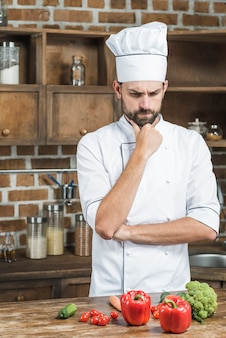Confused cook standing behind the kitchen counter with colorful vegetables