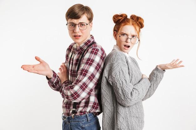 背中合わせに立っている学校のオタクの混乱したカップル